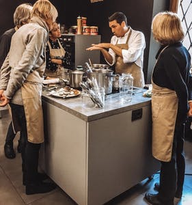 a group of people standing in a kitchen preparing food
